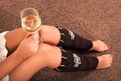 Girl holding wine glass in hands on knees and sitting on carpet floor. Young Girl holding wine glass in hands on knees and sitting on carpet floor. Close up stock images
