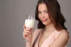 Girl holding a wine glass of milk. Close up. Gray background Stock Image