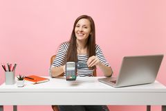 Girl holding wireless modern bank payment terminal to process and acquire credit card payments work at desk with pc royalty free stock photos