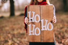 Girl holding wooden board with the text ho ho ho Royalty Free Stock Photography