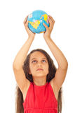 Girl holding world globe over head Stock Image