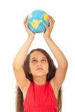 Girl holding world globe over head Stock Image