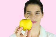 Girl holding a yellow apple Stock Image
