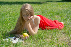 Girl holding a yellow apple and reading a book in a summer park Stock Photography