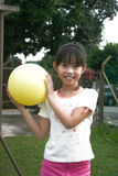 Girl holding yellow ball Stock Photo