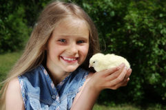 Girl holding yellow chick Stock Images