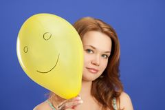 Girl holding yellow smiling balloon Royalty Free Stock Image