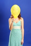 Girl holding yellow smiling balloon Royalty Free Stock Photos