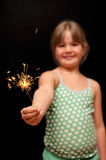 Girl holding yellow sparkler firework with hand. A pretty young girl wearing green polka dot dress holding a yellow sparkler firework with her hand and smiling Stock Photos
