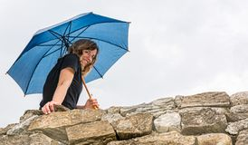Girl holdingan umbrella smiling from a wall Royalty Free Stock Images