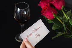 Free Girl Holds A Paper Card With A Message Happy Valentines Day In Her Hand And Red Rose And Wine Glass On Black Table Royalty Free Stock Image - 138234016