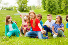 Girl holds airplane toy and children sit behind. Girl holds big white airplane toy and children sit behind her in the field during summer day Stock Images