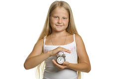 The girl holds an alarm clock in hands Stock Image
