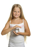 The girl holds an alarm clock in hands Royalty Free Stock Image