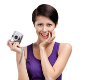 Girl holds amateur hand-held camera. Girl holds amateur hand-held silver camera, isolated on white royalty free stock image