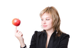 Girl holds an apple on a finger Stock Photos
