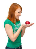 The girl holds an apple in palms. The image of the girl looking at an apple Stock Photography