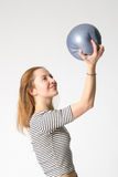 Girl holds ball. Slim smiling fitness young girl holds blue ball on her hand extended upwards and looking at it. Studio shot Royalty Free Stock Photo