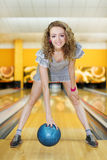 Girl holds ball and stands bending in bowling club Stock Images