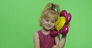 Girl holds balloon in the form of flower. Happy four years old girl. Chroma Key. Positive girl holds balloon in the form of a flower in purple dress. Happy four royalty free stock image