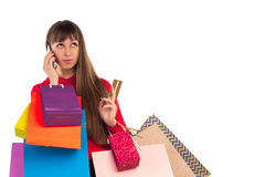 Girl holds banking credit card, colorful shopping paper bags, sm. Young woman with banking credit card, colourful shopping paper bags and packages, smartphone Royalty Free Stock Image