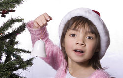 Girl holds bell by the tree. A young girl holds a small bell ornament next to a christmas tree Royalty Free Stock Photos