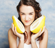Girl holds in really big citrus fruit - pamelo Stock Photos