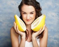 Girl holds big citrus fruit - pamelo, over sky background Stock Photo