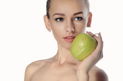 Girl holds a big green apple in front of her face. Stock Image