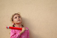 Girl holds big pencil and looks up near wall stock images