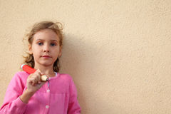 Girl holds big pencil, stands near wall Stock Image