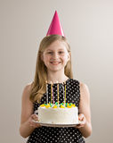 Girl holds birthday cake with lighted candles stock photo