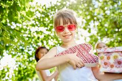 Girl holds birthday gifts with joy. At her birthday party with friends royalty free stock photo