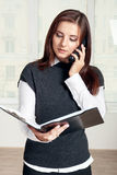 Girl holds a black folder open in one hand and in the other she Royalty Free Stock Photography