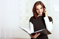 Girl holds a black folder open in one hand and in the other she Royalty Free Stock Photo