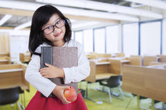 Girl holds book and apple in reading room Stock Photo