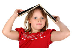 Girl holds a book on her head isolated on white Royalty Free Stock Photo