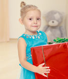 The girl holds the box. The concept of preschool development of the child ,against a child's room where in the background a Teddy bear.Caucasian little girl in a Stock Photo