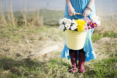 The girl holds a bucket with flowers. The girl keeps a bucket with flowers in gumboots Royalty Free Stock Images