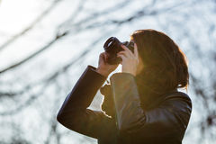 The girl holds a camera in her hands and takes a picture Stock Photos