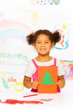 Girl holds carton card with Xmas tree and stands Stock Photos