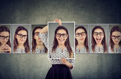 Girl holds and changing her face portraits with different expressions stock photos