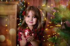 The girl holds a Christmas ball in hand. The girl holds in hand a Christmas ball near a Christmas tree Stock Photos