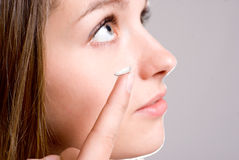 A girl holds a contact lens. Focus on the lens Stock Photos