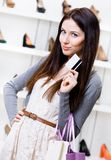 Girl holds credit card in footwear shop Royalty Free Stock Image