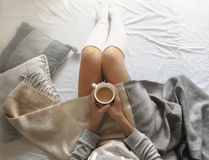 Girl holds a cup of hot coffee on a cold winter morning at home in bed. Girl holding a cup of hot coffee on a cold winter morning at home in bed stock image