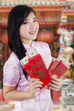 Girl holds dollar cash in envelope at the temple Royalty Free Stock Images