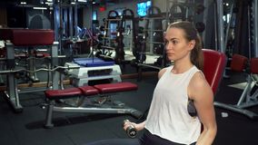 A hard-working girl is training her arms with dumbbells. The girl holds a dumbbell in each hand. She lowers and raises her hands. The girl is sitting on a stock video footage
