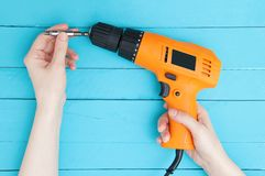A girl holds a electric screwdriver and a bit stock photography