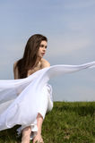 Girl holds fabric in hands waving in the wind Stock Photo